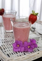 Two smoothies in a glass with strawberry